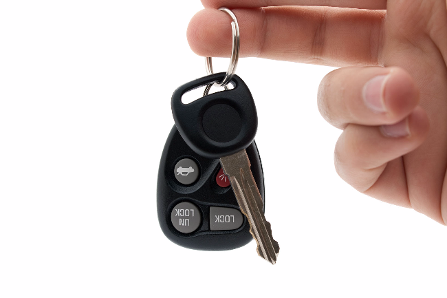 a-hand-holding-car-keys-and-a-remote-control-for-keyless-entry-i.jpg